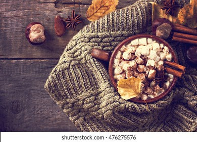 Hot cocoa with marshmallows with spices on the old wooden boards. Coffee, cocoa, cinnamon, nuts, star anise, cozy sweater