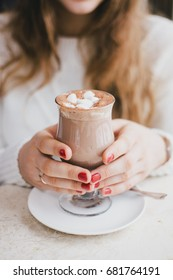 Hot cocoa with marshmallows in a woman's hands