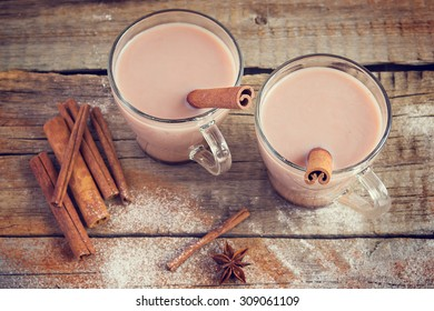 Hot cocoa on an old wooden table, cinnamon sticks, star anise