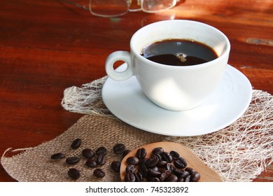 Hot coffee americano in a white cup on a wooden table.