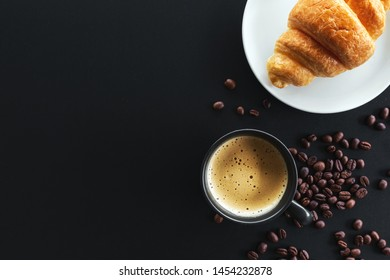 hot coffee, bean and butter croissants on black table with soft-focus and over light in the background