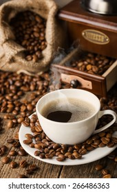 hot coffee and coffee beans on the background of coffee grinders