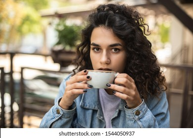 Hot coffee. Beautiful young girl drinking tea or coffee in cafe. Beauty model woman with the cup of hot beverage. There is place for your logo on the cup.
