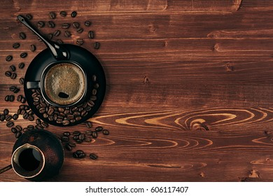Hot coffee in black cup with beans, spoon and turkish pot cezve with copy space on brown old wooden board background, top view.  Rustic style.