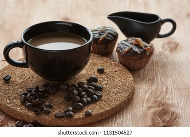 Hot coffee in a black cup and chocholate cupcakes on the wooden table
