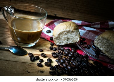 Hot coffee and bread on a wooden table. Dark background.