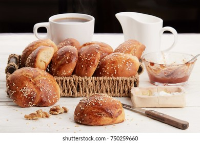 Hot coffee with buns, milk, butter and jam