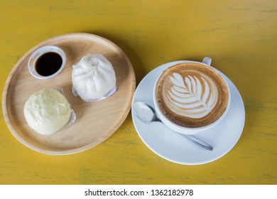 Hot coffee and hot buns placed on a wooden table, snacks