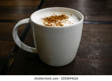 Hot coffee cappuccino mug with cinnamon powder sprinkle on top milk foam on dark wood table blurred background, close up.