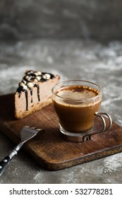 Hot coffee and chocolate mousse cake  with hazelnuts and dark chocolate glaze on a wooden and grey stone background.  Dark food photography