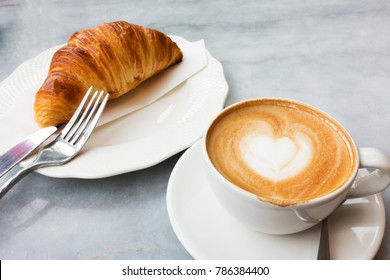 Hot coffee and croissants on a marble table.