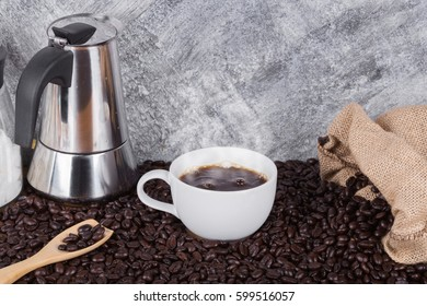 hot coffee in cup with beans and geyser coffee maker