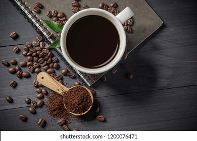 Hot coffee cup with coffee beans and the ground powder of coffee on the wooden table