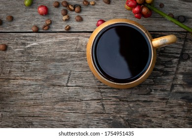 Hot coffee cup and coffee beans on the wooden table with copy space.