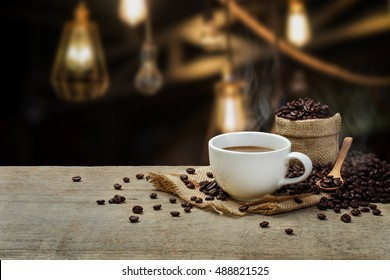 Hot Coffee cup with Coffee beans on the wooden table in the shop background.