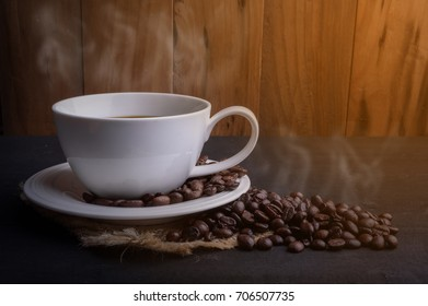 Hot Coffee cup and coffee beans on wooden background.