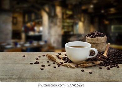 Hot Coffee cup and coffee beans roating on the wooden table and the coffee shop background with copy space