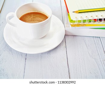 Hot coffee cup with a book and pencil on white wooden