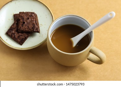 Hot coffee cup and brownie on brown background.