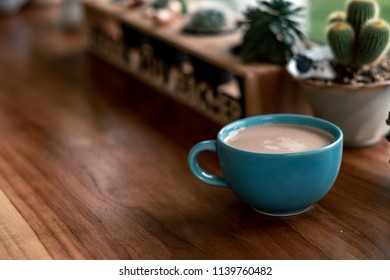 hot coffee cup with cactus on pottery decoration objects.hot coffee mug on white table.