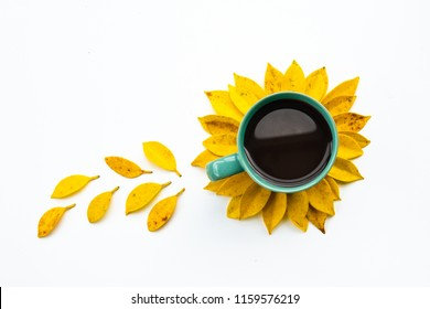 hot coffee cup with creative arrangement yellow leaf.sunflower made by yellow leaves and coffee cup.flat lay.