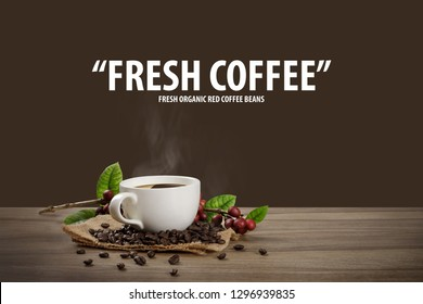 Hot coffee cup with fresh organic red coffee beans and coffee roasts on the wooden table and the brown background with copy space for your text.