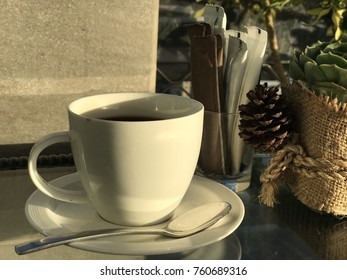 Hot coffee cup on breakfast table with pine cones