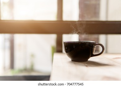 hot coffee cup on table,breakfast beverage in the morning,selective focus and sun flare