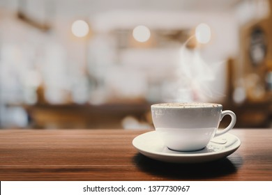 Hot coffee cup on wood table in coffee shop or cafe for background.