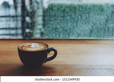Hot coffee cup on wooden table by the windows in rainy day.