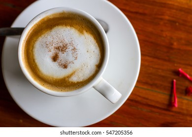 Hot coffee in cup on wooden table