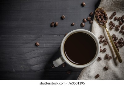 Hot coffee cup with the roasted coffee beans on the wooden table with copy space