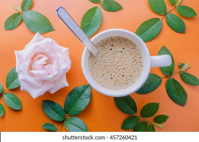 Hot coffee in a cup and Rose pink flower on an orange background with top view.