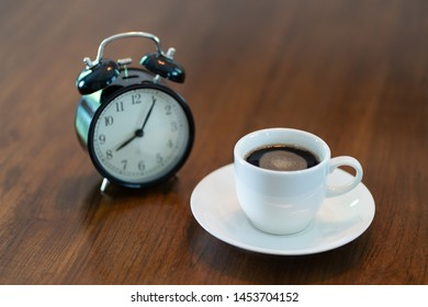Hot coffee cup and vintage clock time at 8 o'clock in the morning