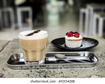 Hot coffee with cupcake raspberry on the concrete table,blurred background