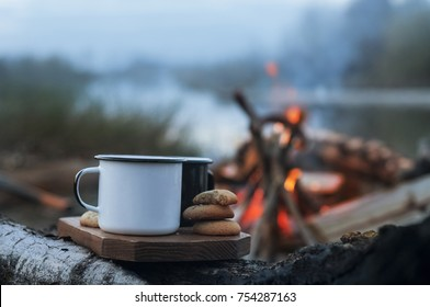 Hot Coffee cups and cookies  on wooden desk, near campfire. Morning light.