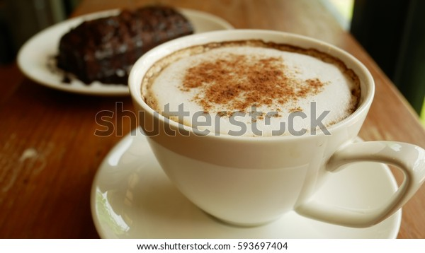 Hot coffee with foam milk. Cappuccino coffee on wooden table and brownie background. A light side. Vintage style.