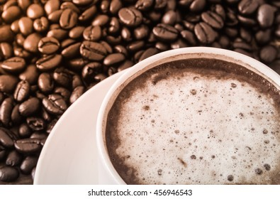 hot coffee with foam on top and bean background lighting tone