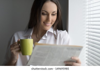 Hot coffee and fresh news. Beautiful young woman reading newspaper and drinking coffee