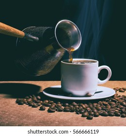 Hot coffee. Coffee grinder, turk and cup of hot coffee with coffee beans and saucer on a brown table. Dark background