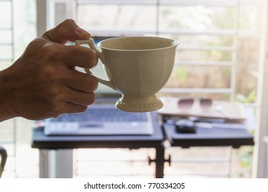 hot coffee hold by man hand with leak light
