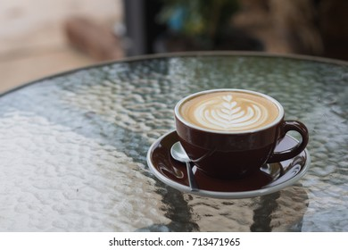 hot coffee latte with beautiful foam art on glass table.outdoor cafe.