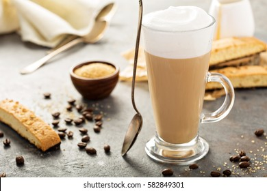 Hot coffee latte with brown sugar and biscotti cookies in tall glass.