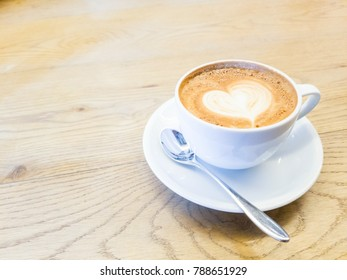 Hot Coffee Latte with a heart shape in the cream foam for Valentines Day and copy space. (Love concept)
