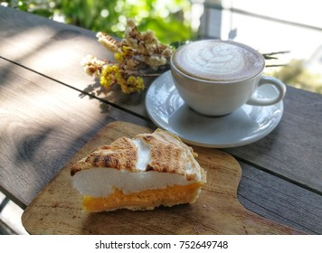 Hot coffee latte in white cup and lemon meringue pie dessert on brown wood table.