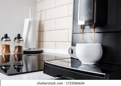 hot coffee from the coffee machine is poured into a white porcelain Cup