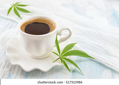 Hot coffee and marijuana leaves on a table