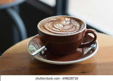 Hot coffee mocha with beautiful latte art topping with choccolate powder on ceramic glass in local indy coffee cafe at Thailand.