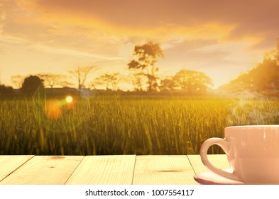 hot coffee on wooden table meadows at sunrise