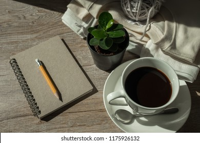 hot coffee on wooden table in the morning.espresso in the winter season. Relax time in the winter. pencil and notebook with hot coffee in the morning. Perfect for winter.coat,Yarn,coffee,notebook.